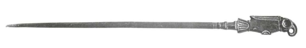 Es handelt sich um eine 15 cm lange bronzene Schmucknadel, deren oberes Endes einen Vogel darstellt (Tiroler Landesmuseum Ferdinandeum).